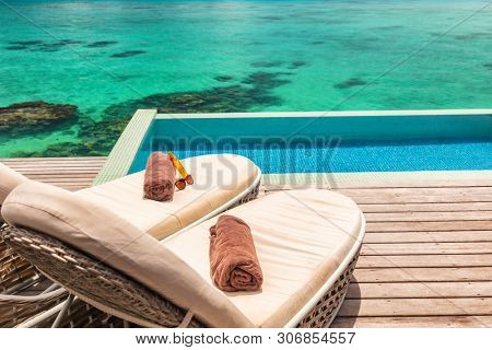 Luxury hotel infinity swimming pool with two sun loungers on deck with towels for couple's honeymoon relaxing overwater bungalow suite. Ocean reefs blue background.