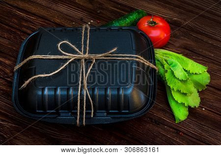 Black Lunch Box Tied With Flagella. Food On Dark Brown Wooden Surface. Closed Box For Food, Tomato,