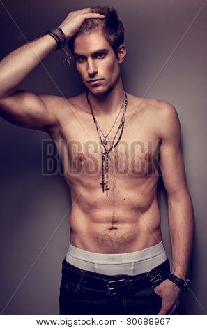 Handsome sexy bare chested man wearing a cross around his neck and posing showing off his muscles with his hand to his head.