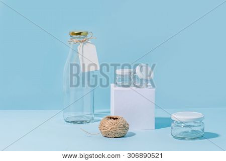 Composition Of Glass Jars On Pedestal, Tagged Empty Milk Bottle And Hank Of Twine Over Blue Backgrou