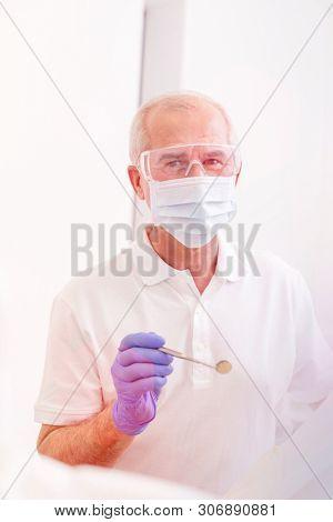 Portrait of senior dentist holding angled mirror at dental clinic