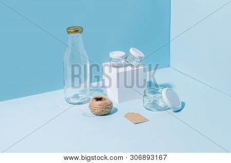 Composition of glass jars on pedestal, empty milk bottle, hank of twine and blank tag in the corner over blue background poster