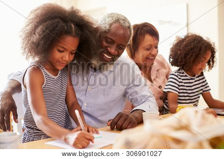 Grandparents Sitting At Table With Grandchildren Playing Games Together