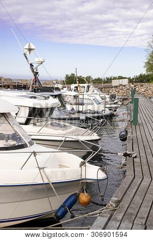Docked Boats. Moored Boats. Boats Standing In A Row At A Wooden Pier. Docked Boats