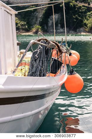 Orange Buoys Hanging From The Side Of A Small Private Fisherman Boat Moored In Port Near Keri Beach