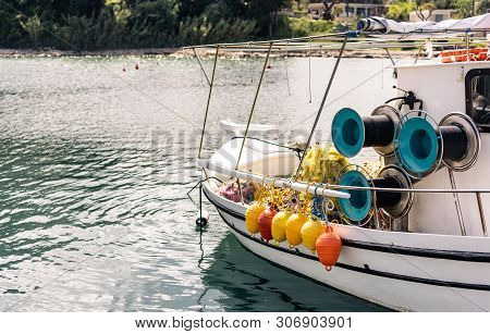 Orange And Yellow Buoys Hanging From The Side Of A Small Private Fisherman Boat Moored In Port Near