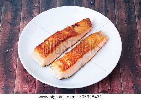 2 Grilled Salmon Steaks On White Plate Served On Wood.