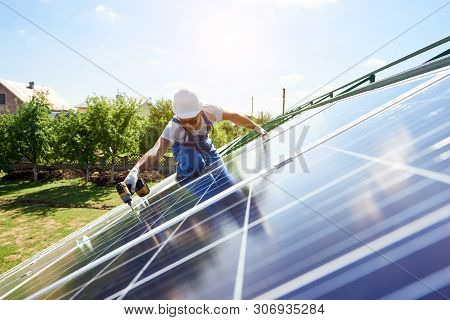 Worker Mounting Solar Panels For Renewable Energy On Houses Roof. Using Special Equipment, Wearing P