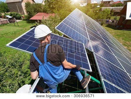 Standing On High Metallic Ladder, Worker Keeping Solar Panel. Installing Solar Batteries Screen On H