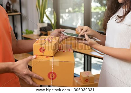 Customer Sign Signature In Digital Tablet After Receiving Parcel From Delivery Courier At Home.