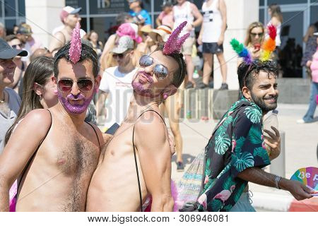 The Annual Parade Lgbt. Gay Men Walking In The Gay Pride Parade. Parade Of Tolerance. Rainbow Flags