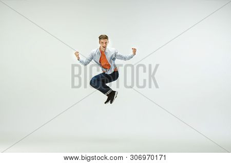 Happy Young Man Working At Office, Jumping And Dancing In Casual Clothes Or Suit Isolated On White S