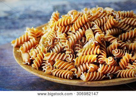 Wholemeal Fusilli In A Plate. Integral Pasta Over A Wooden Table