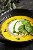 Exquisite Serving Pumpkin Cream Soup with Ricotta Cheese Mousse. Beautiful Creative Molecular Italian Dish with Stylish Decorations of Dark Plants on Natural Black Stone poster