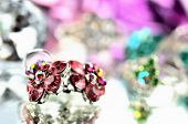 Close-up of red flower shaped earrings with red diamonds and ring jewelery - reflection effect - colored backgrounds - purple - warm color balance poster