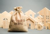 Money bag with the words Utility bill debts and wooden houses. Fines and penalties for failure to pay the debt for electricity and gas. Register of debtors. Stopping the provision of utilities. poster