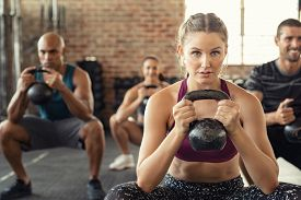 Group of fit people holding kettle bell during squatting exercise at gym. Fitness girl and men lifting kettlebell during strength training exercising. Young people doing squat with heavy kettlebells.