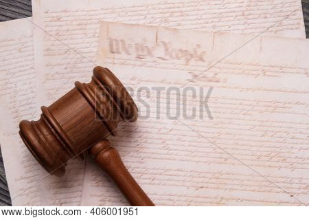 Close-up Wooden Gavel And Old Text. Papers With Elder Text And Court Judge Hammer.