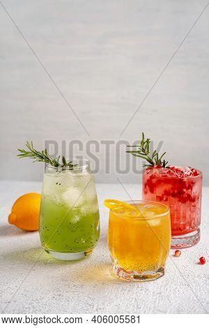 Three Colorful Summer Cocktails In Glasses On White Table. Assortment Of Fresh Summer Drinks. Red Sa
