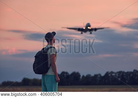 Young Man Looking Up At Flying Airplane Against Moody Sky During Dusk. Themes Nostalgia For Travel A