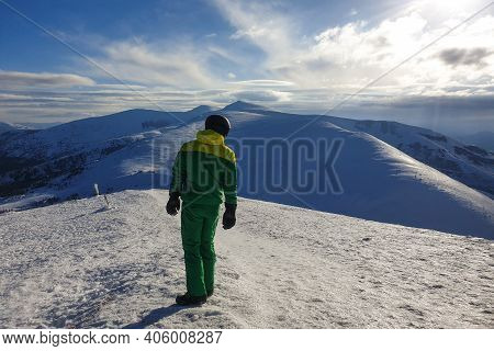 Male Trekker Standing On A Top Of The Mountain While Observing The Horizon. Beautiful Blue Sky In Ba