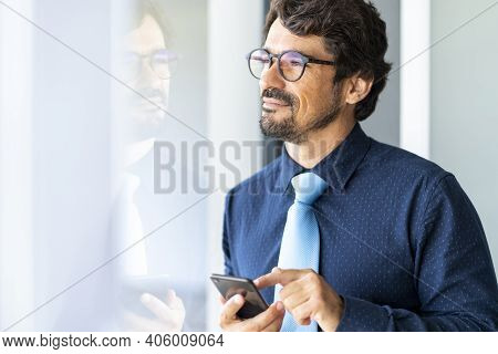 Businessman Wearing Glasses Looking Through Window Holding His Cell Phone. Successful Male Portrait
