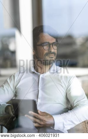 Businessman Wearing Glasses Sitting Down Holding His Tablet And Looking Through The Window. Successf
