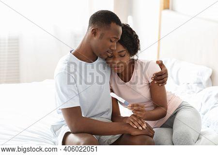 Upset Black Couple Holding Negative Pregnancy Test, Husband Hugging His Depressed Wife, Bedroom Inte