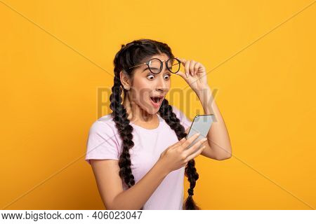 Wow, Great News. Portrait Of Excited Surprised Indian Woman Holding And Using Smartphone, Browsing S