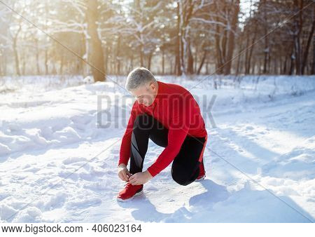 Mature Jogger In Warm Sportswear Tying Shoelaces On Snowy Road At Winter Park. Senior Man Going For