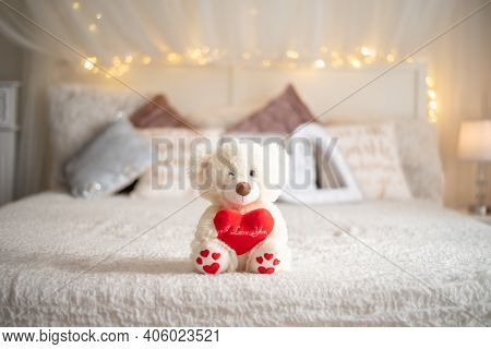 Teddy Bear Hug Heart Pillow On Bed, Valentines Day Concept