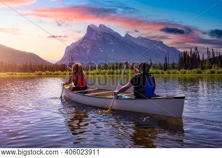 Couple Adventurous Friends Are Canoeing In A Lake Surrounded By The Canadian Mountains. Colorful Sun