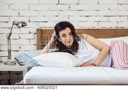 Girl Lying On A White Pillow And A Mattress On A Wooden Bed. Concept Of Comfortable Sleep. Orthopedi
