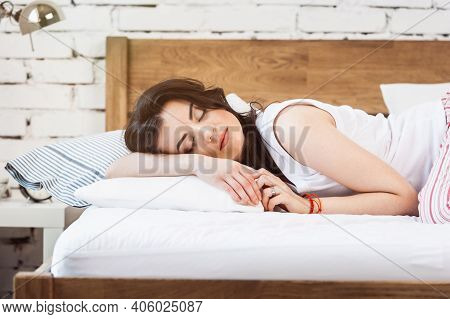 Woman Sleeping On A White Pillow And A Mattress On A Wooden Bed. Concept Of Comfortable Sleep. Ortho