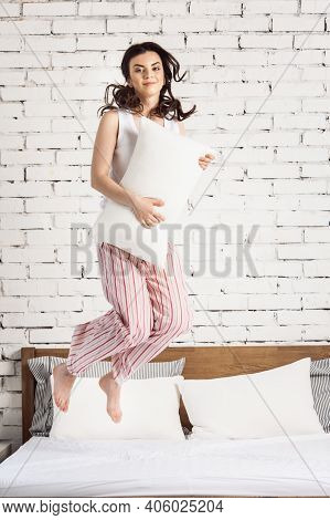Girl With A White Pillows In Hands Jumping On A Bed, White Bricks Background. Concept Of Comfortable
