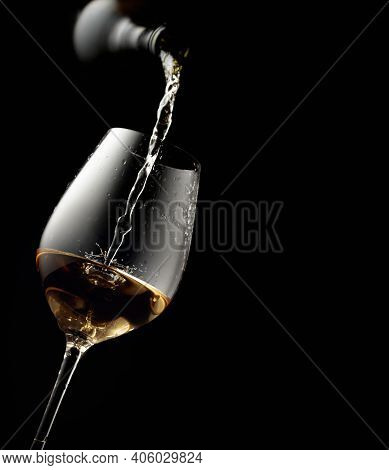 Pouring White Wine In A Glass Goblet. Black Background With Copy Space.