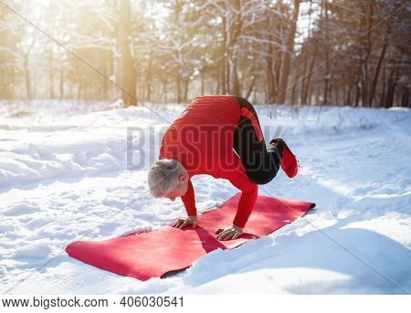 Fit Senior Man Having Outdoor Yoga Practice In Winter At Snowy Forest. Mature Guy Standing In Crow O
