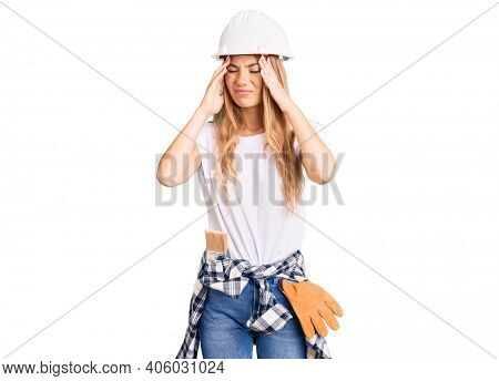 Beautiful caucasian woman with blonde hair wearing hardhat and painter clothes suffering from headache desperate and stressed because pain and migraine. hands on head.