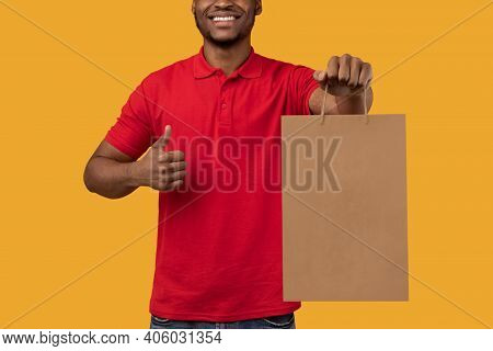 Closeup Of Unrecognizable Black Man In Red T-shirt Holding Craft Paper Bag, Showing Thumbs Up Gestur