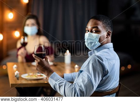 Lockdown Date. Young Interracial Couple In Protective Medical Masks Having Romantic Dinner In Restau