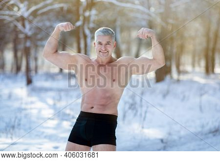 Handsome Senior Man With Bare Torso Showing His Strong Biceps In Winter Frost At Snowy Forest. Happy
