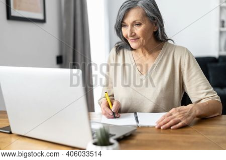 Charming Mature Mid-aged Woman Watching Online Webinars On The Laptop Sitting At The Table At Home,