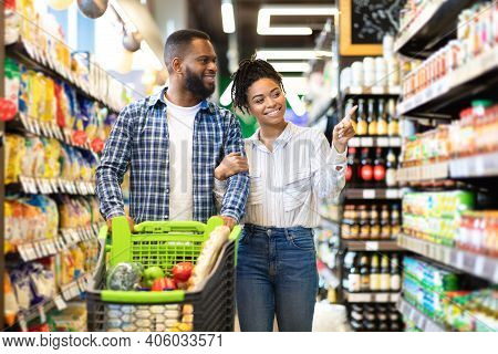 Cheerful Black Spouses Choosing Food In Grocery Store Walking With Cart Full Of Products Along Super