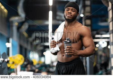 Rest After Workout. Shirtless African American Bodybuilder Holding Water Or Protein Drink And Towel