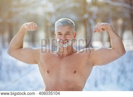 Handsome Senior Sportsman With Snow On His Face And Bare Torso Showing Prominent Biceps Muscles Outd