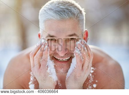 Happy Senior Man Washing His Face With Snow, Developing Resistance To Cold At Frosty Winter Park. Ch