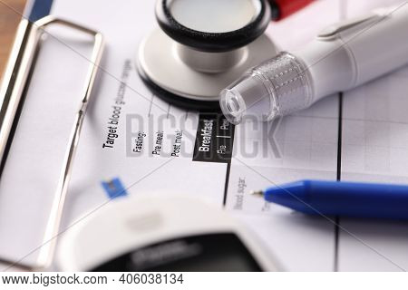 Lancet And Blood Glucose Meter Lying On Clipboard With Medical Documents Closeup. Diagnosis And Trea