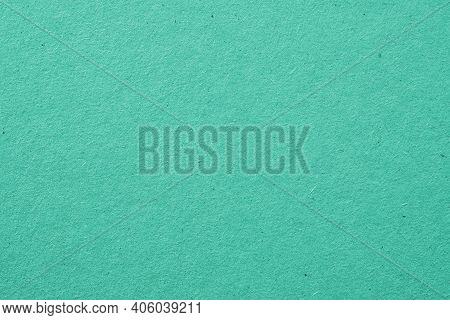 The Surface Of Turquoise Cardboard. Rough Paper Texture With Cellulose Fibers. Saturated Aquamarine.