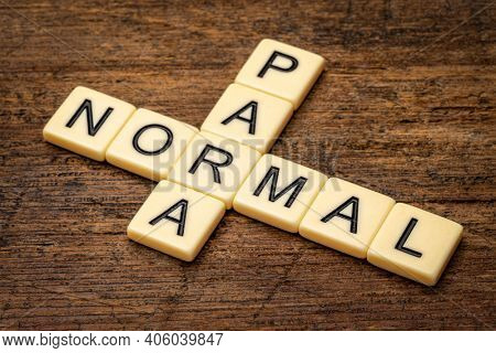 paranormal crossword in ivory letter tiles against rustic weathered wood, supernatural and unexplained phenomena