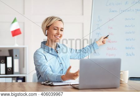 Online Foreign Languages Tutoring. Joyful Female Teacher Giving Italian Class, Pointing At Blackboar